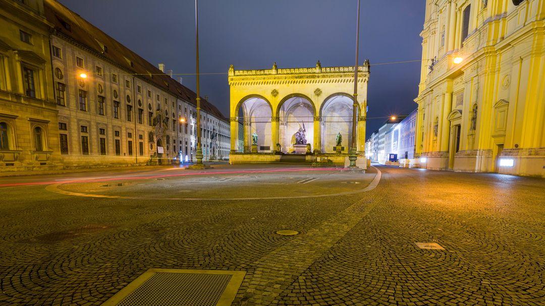 Menschenleerer, erleuchteter Odeonsplatz mit Blick auf die Feldherrnhalle, links die Residenz, rechts die Theatinerkirche