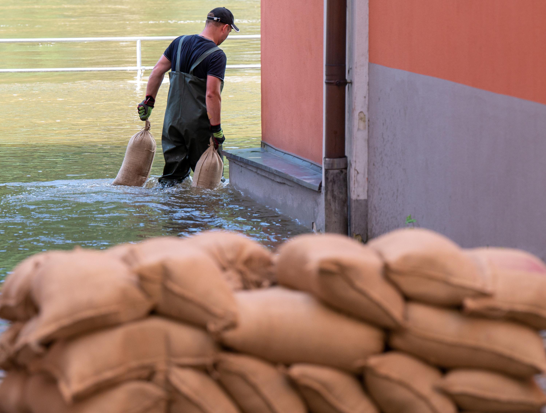 18.07.2021, Bayern, Passau: Ein Mann trägt Sandsäcke um Abdichten von Türen und Fenstern durch das Wasser der Donau, das auf der Uferpromenade der Stadt steht. In Passau steigen die Wasserstände der Flüsse stündlich weiter an.