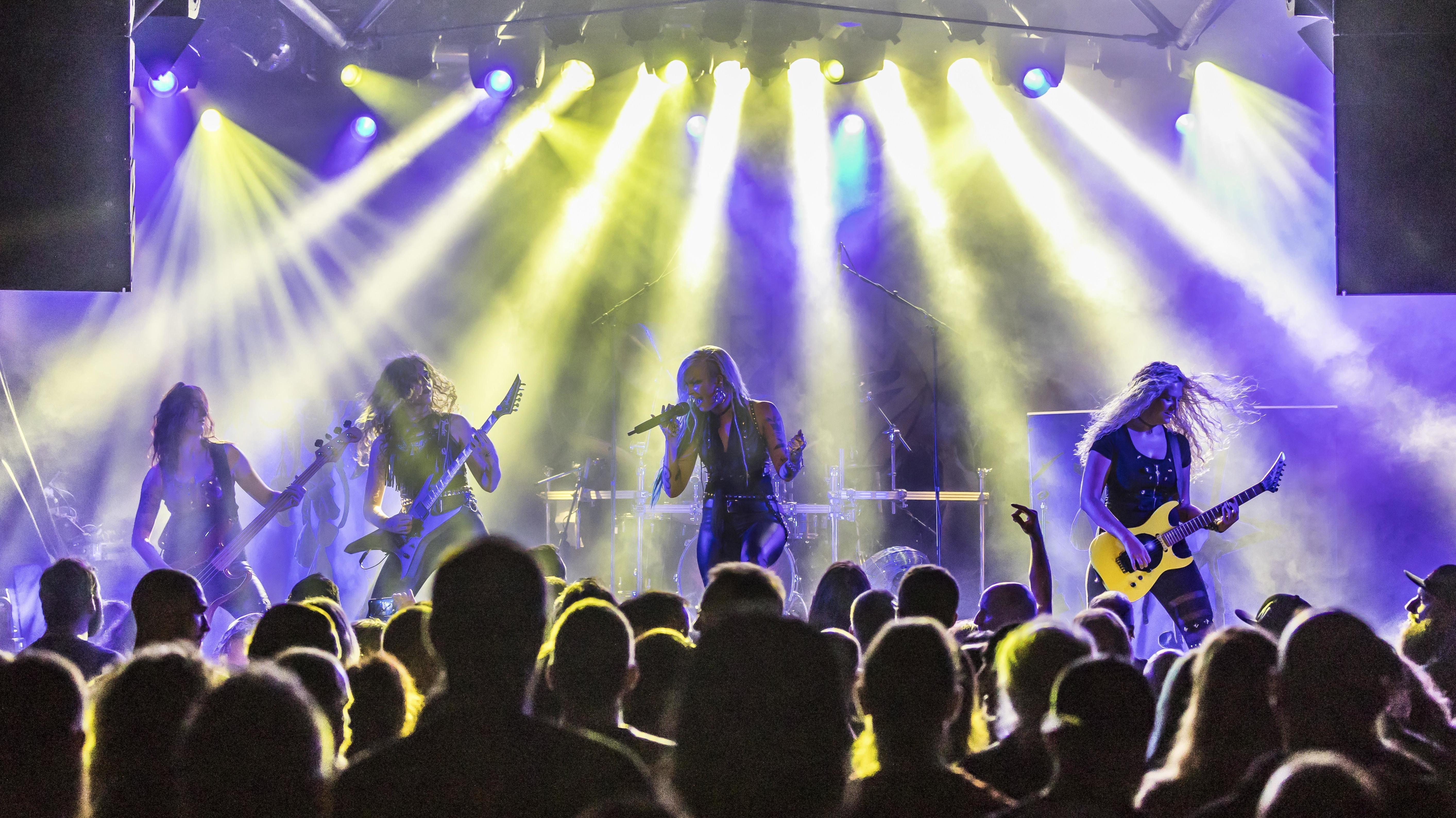 Eine Rock-Band spielt auf der Bühne, davor Publikum.