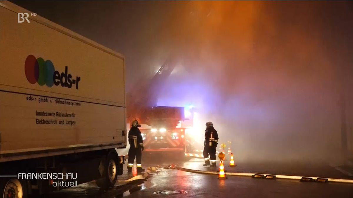 Zwei Feuerwehrleute neben einem Wasserschlauch in der verqualmten Nacht.