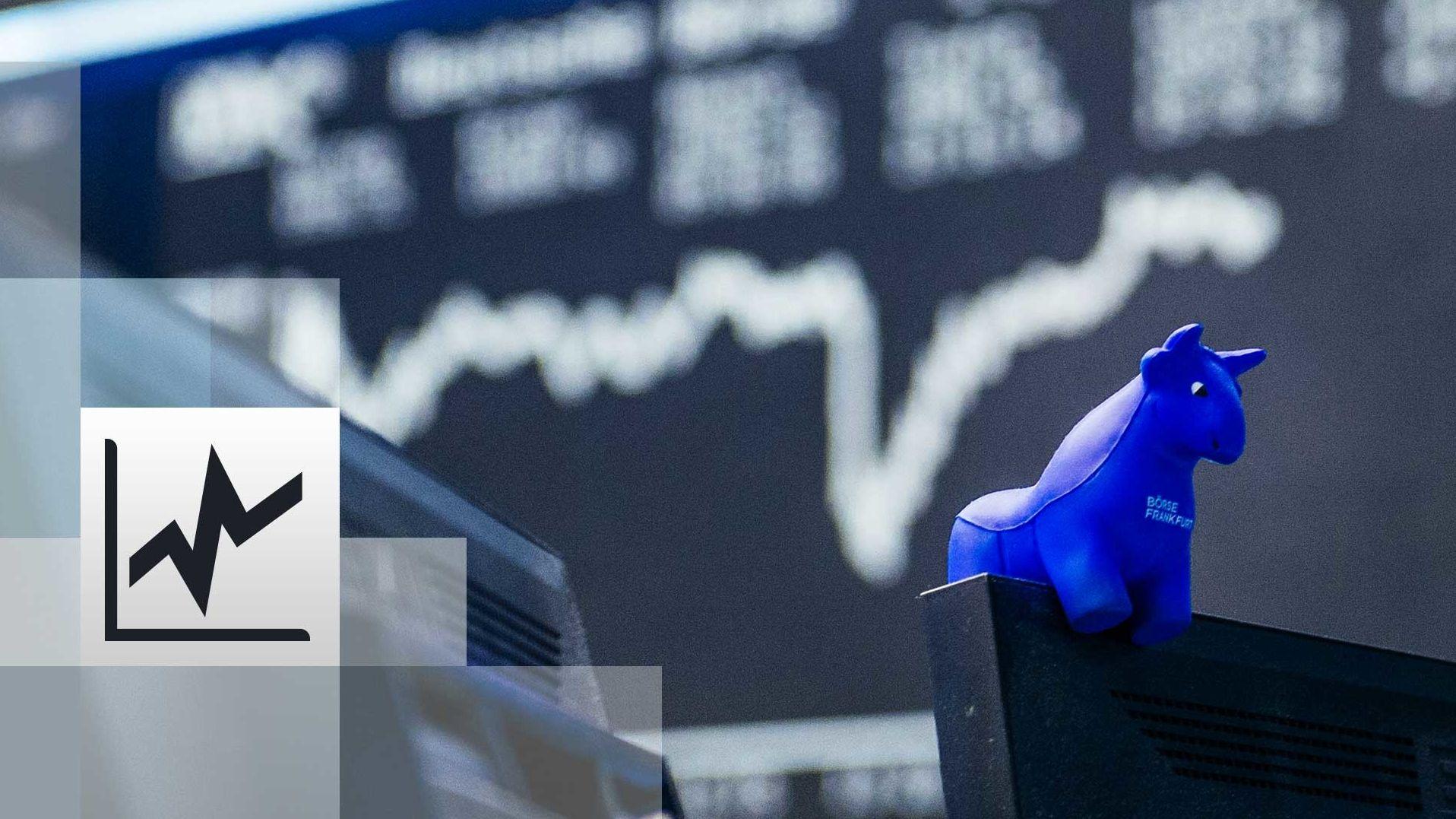 in blauer Stier aus Gummi sitzt auf der oberen Kante eines Bildschirmes, im Hintergrund die Kurstafel der Börse