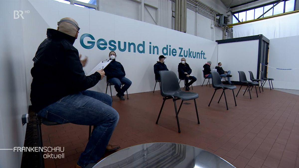 """Sechs Männer sitzen auf Stühlen und warten, dahinter eine Wand mit der Aufschrift """"Gesund in die Zukunft""""."""