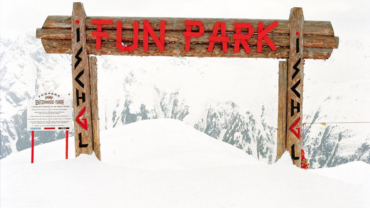 """Tor aus Holzlatten auf einem Schneeberg vor dem Alpenpanorama: Darauf steht in roten Lettern """"Fun Park""""."""