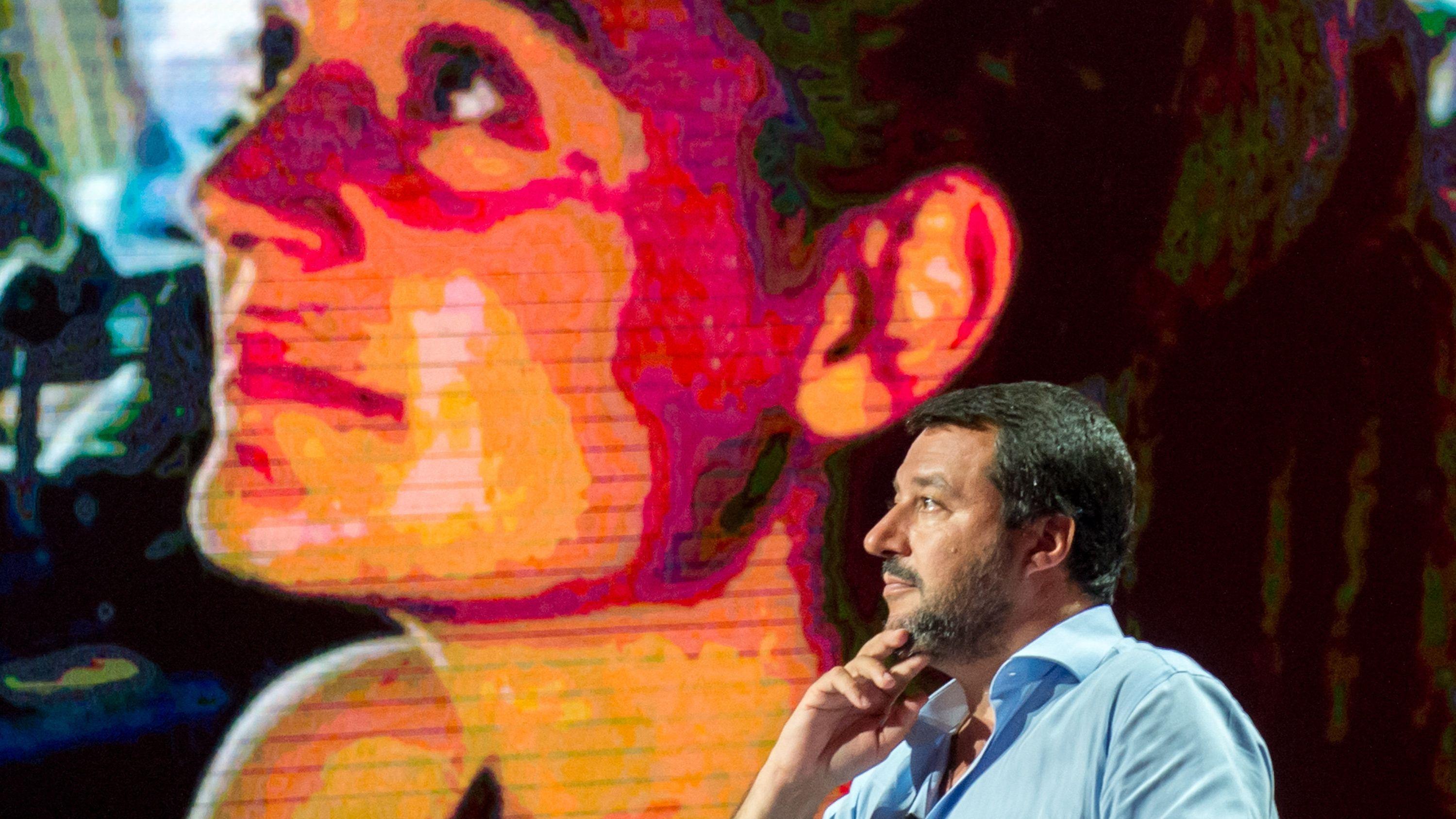 """Matteo Salvini, Innenminister von Italien, spricht während einer TV-Sendung. Auf der Monitorwand im Hintergrund ist die Kapitänin Carola Rackete des Rettungsschiffs """"Sea Watch 3"""" eingeblendet"""