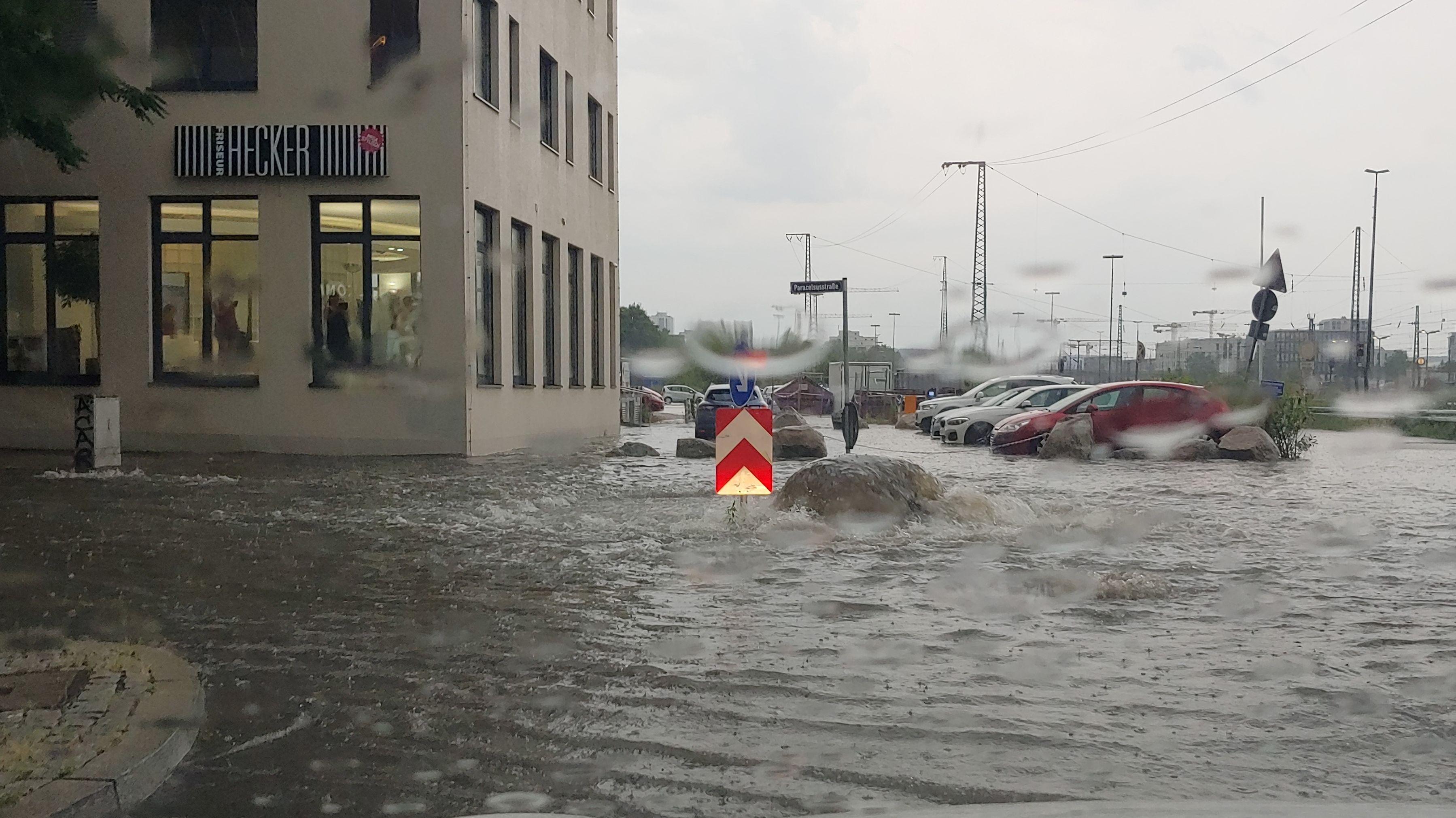 Überschwemmte Straße und übergelaufener Gulli bei den Arcaden in Regensburg