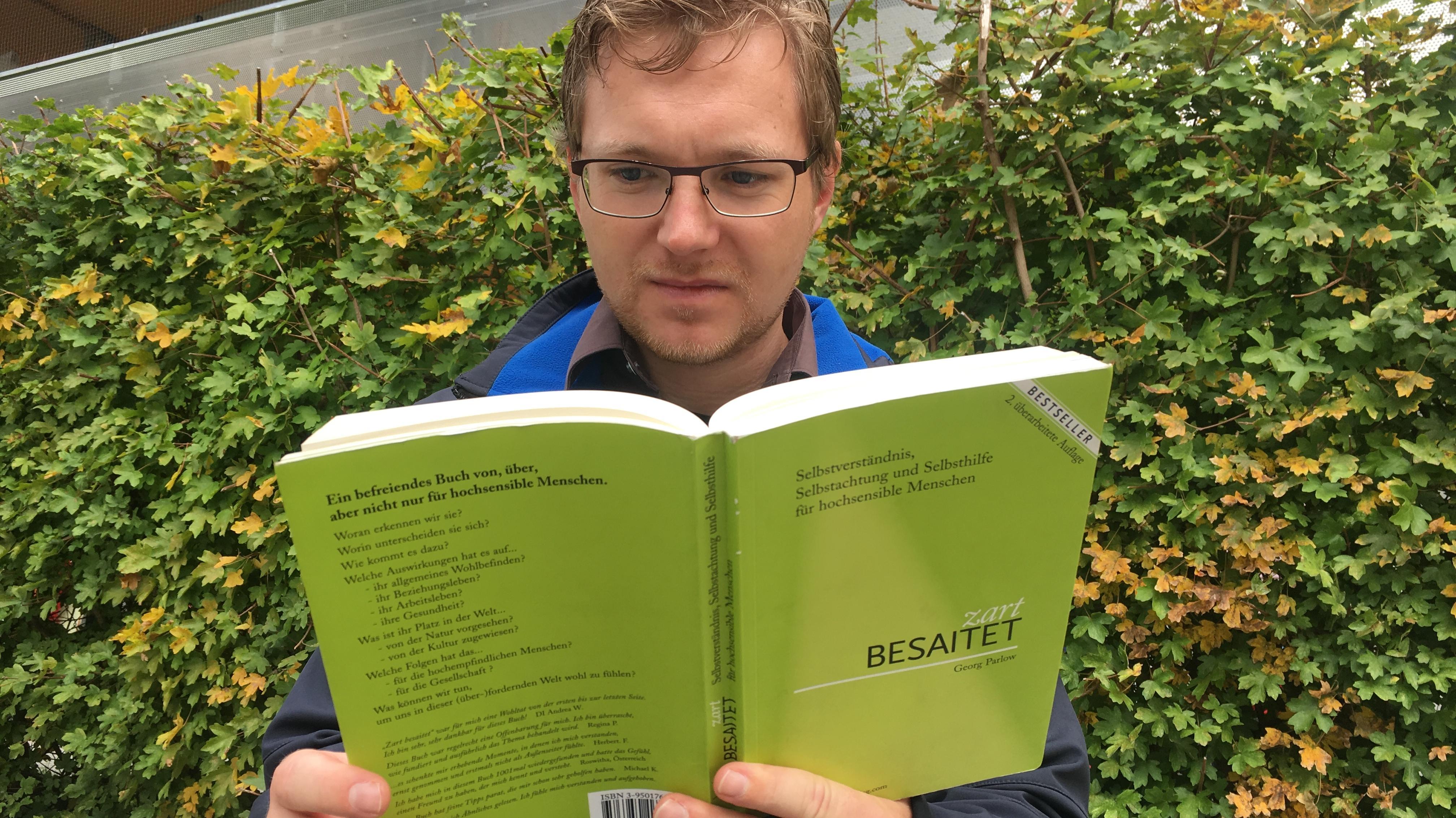 """Mann liest das grün eingebundene Buch """"zart beseitet"""""""