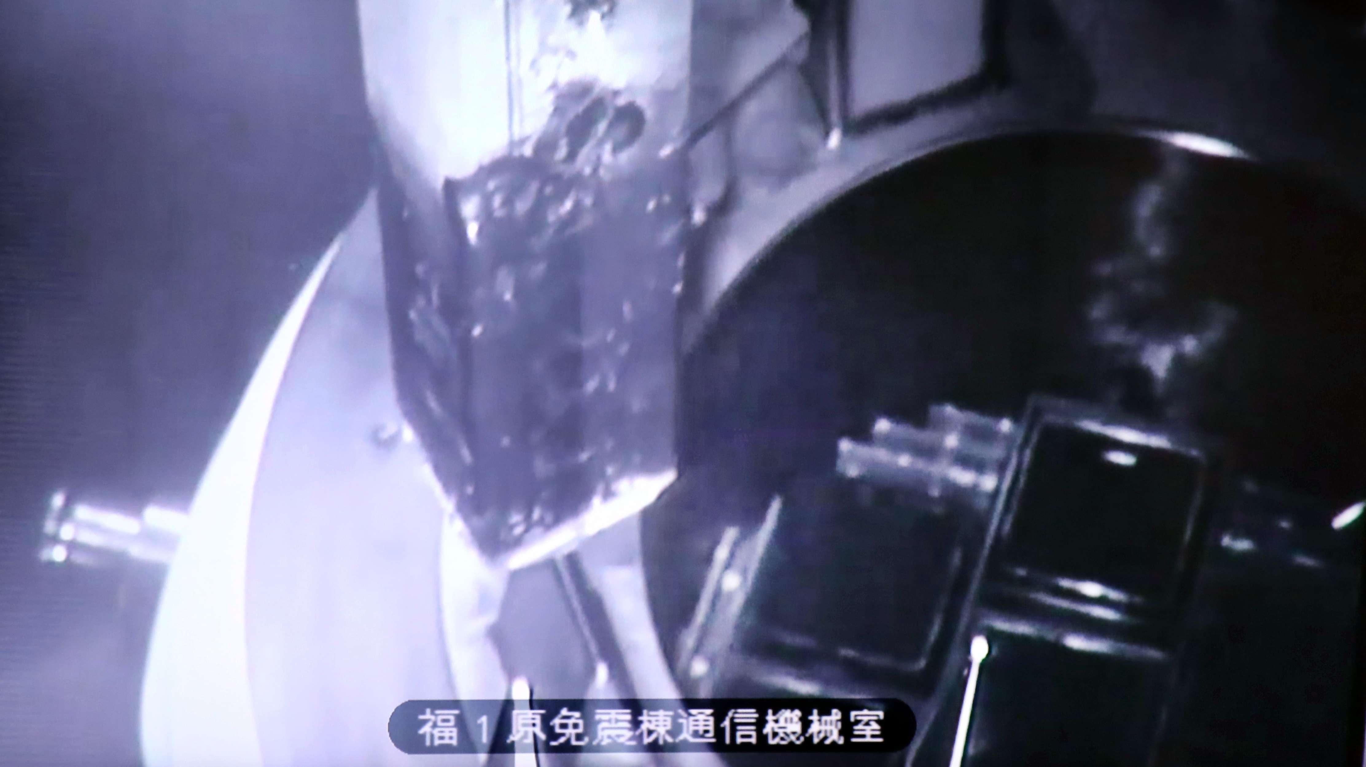 Auf einem Monitor ist zu sehen: Die Entfernung der Brennstäbe aus dem Abklingbecken des Reaktors 3 in Okuma, Fukushima.