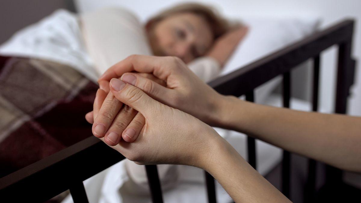 Patient liegt im Bett, jemand hält seine Hand