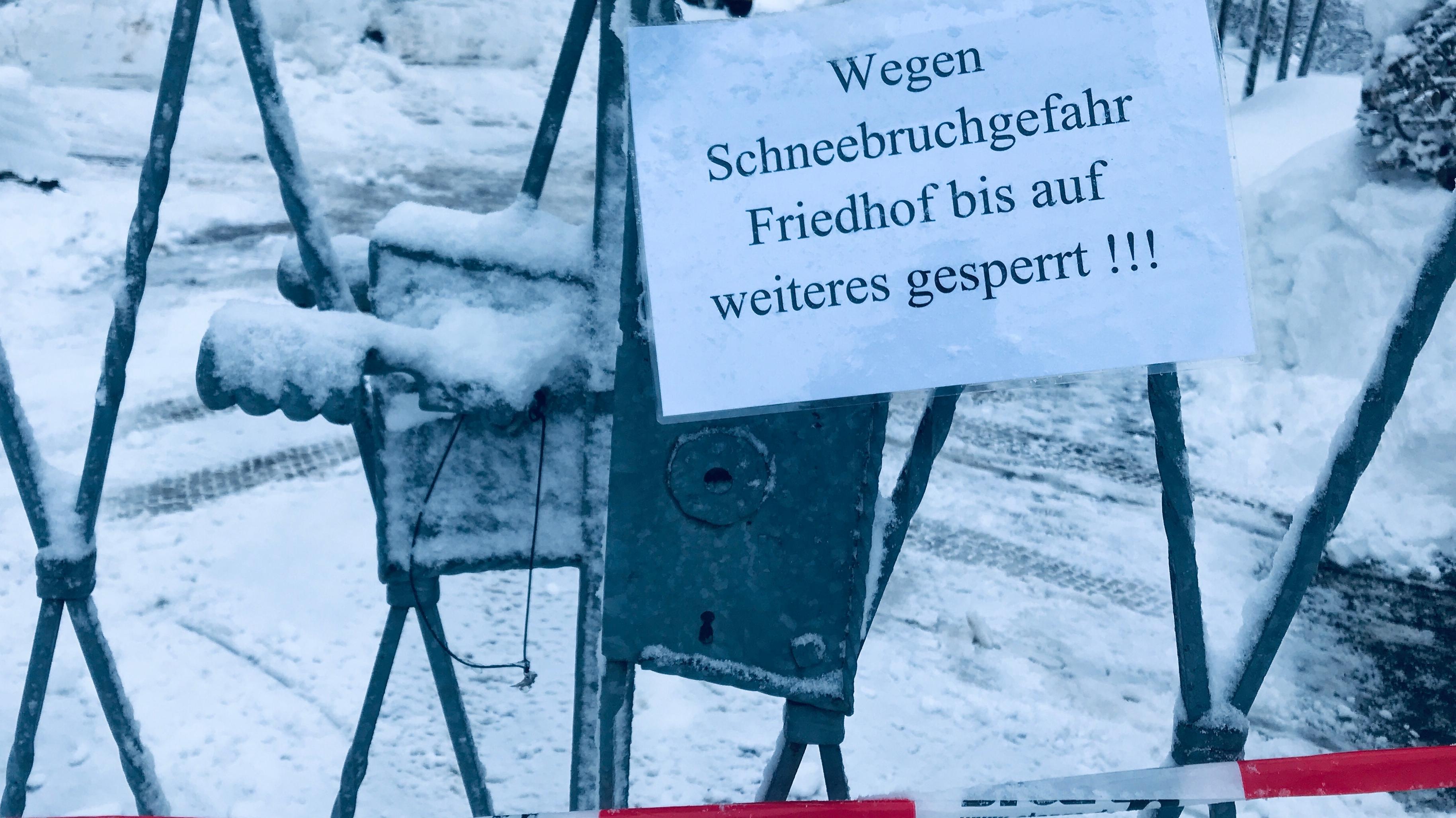 Schild zeigt: Wegen Schneebruchgefahr Friedhof bis auf weiteres gesperrt.