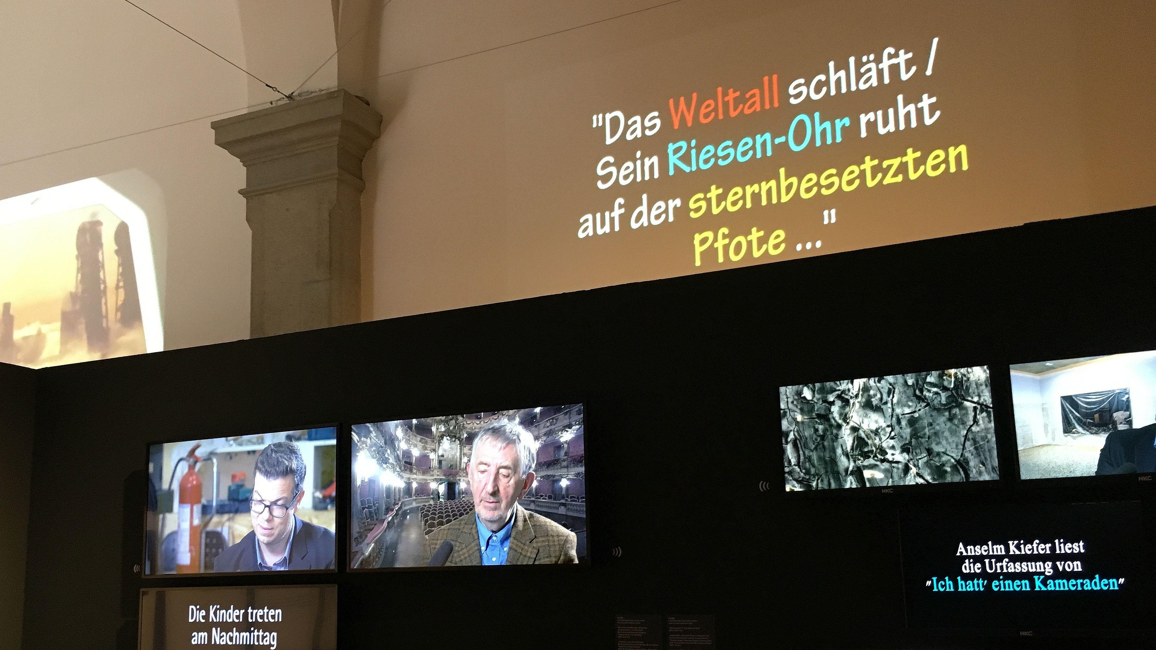 """Vier Monitore mit Interviewpartnern wie dem Dichter Ben Lerner und dem Sprachwissenschaftler Hans Belting und bunte Schrift in Stummfilm-Art: """"Das Weltall schläft. Sein Riesen-Ohr ruht"""""""