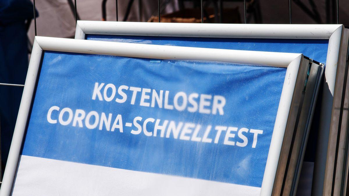 """Ein Schild mit der Aufschrift """"Kostenloser Corona-Schnelltest"""" steht vor einem Testzentrum (Symbolbild)."""