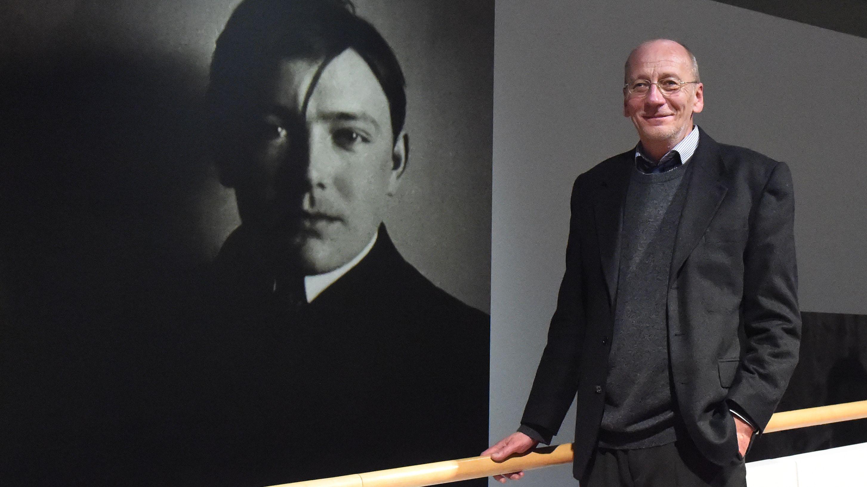 Hans-Georg Küppers posiert vor einem Foto des Künstlers August Macke