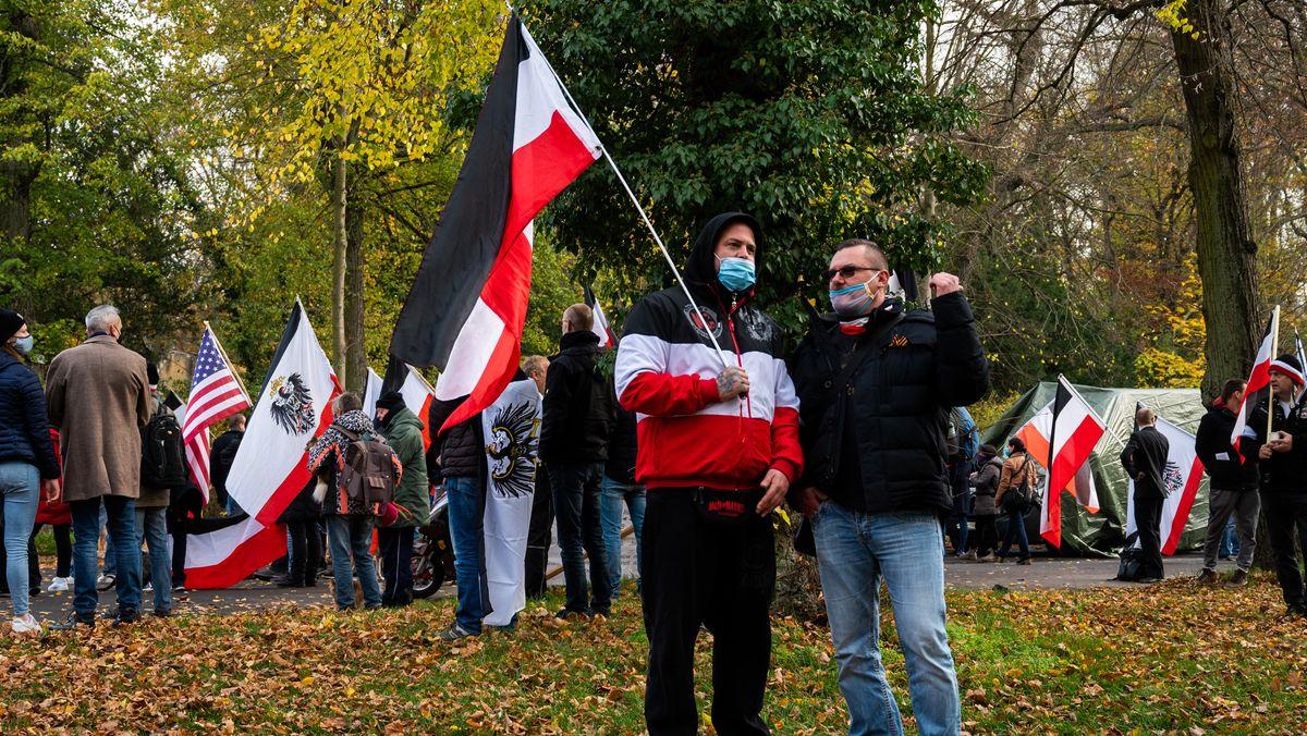 Ein Demonstrant trägt eine schwarz-weiß-rote Fahne. Laut einer Studie verschärft die Corona-Pandemie den Rechtsextremismus in Europa.