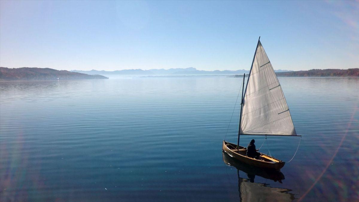Segelboot auf dem Starnberger See mit Blick auf die Alpen.