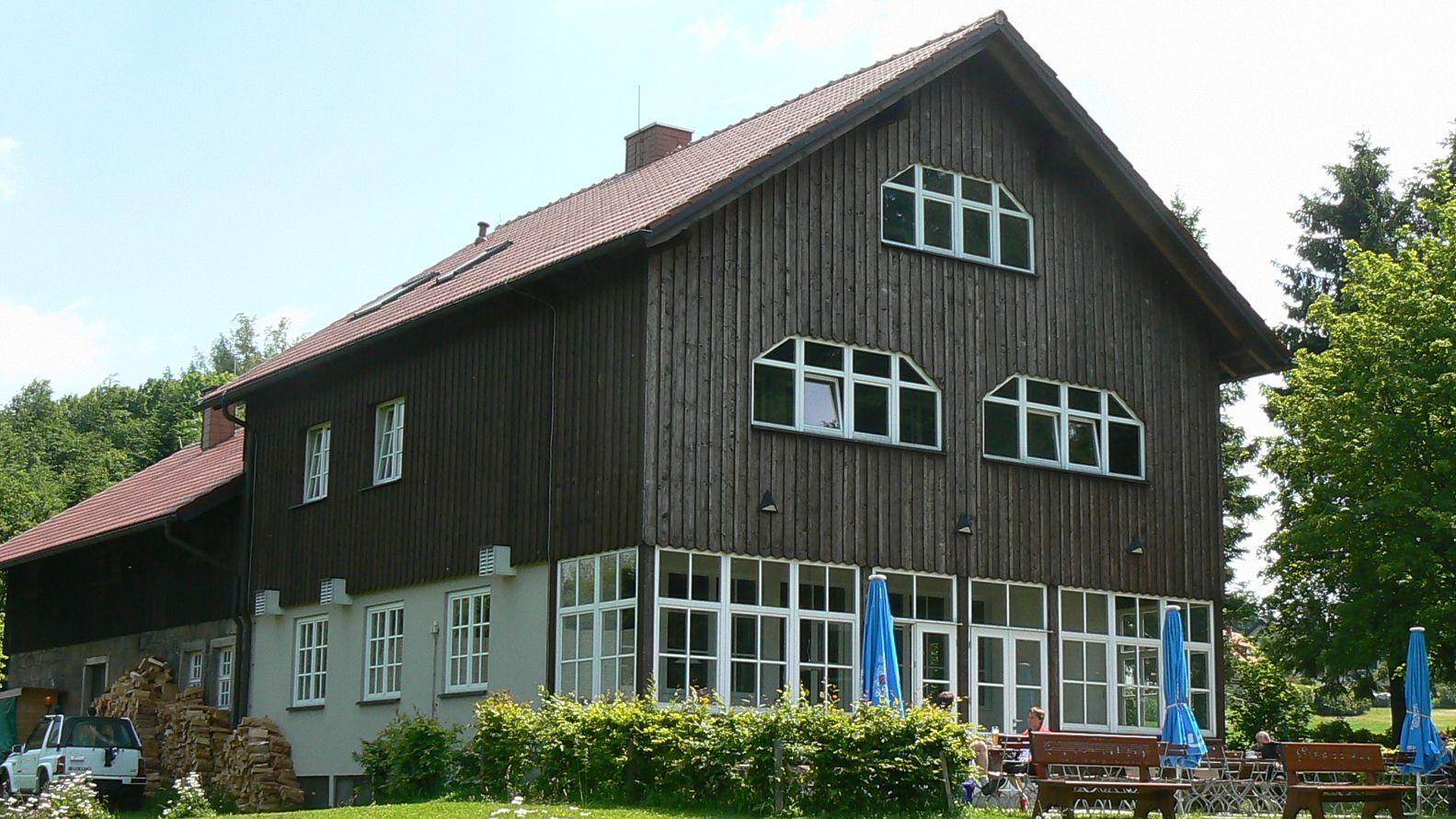 Das Marktredwitzer Haus ist mit Holz vertäfelt, auf der Terrasse stehen Bänke und Tische und drei blaue Sonnenschirme.