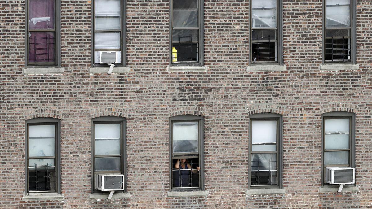 Eine Fensterfront an einem Apartmentblock in der Bronx in New York, aus einem der Fenster blickt eine Frau