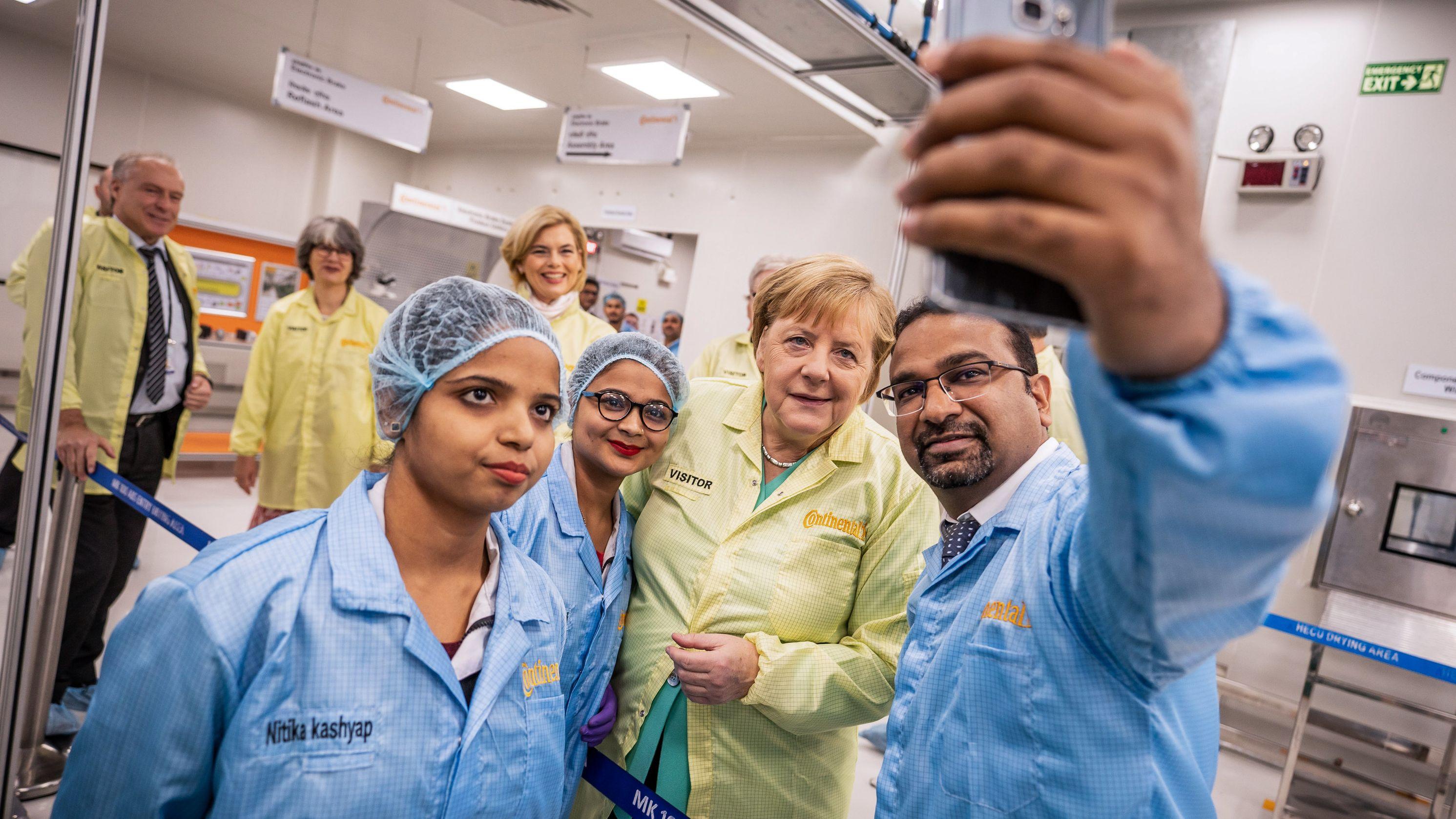 Bundeskanzlerin Angela Merkel (M, CDU), macht ein Selfie mit Mitarbeitern beim Besuch der Continental Automotive Components India.