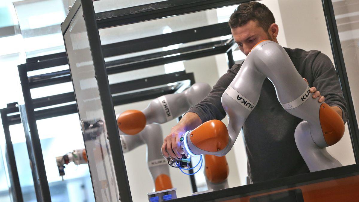 Ein Kuka-Mitarbeiter richtet einen Roboterarm aus