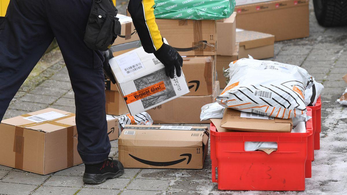 Ein Paketzusteller sortiert Pakete auf dem Boden