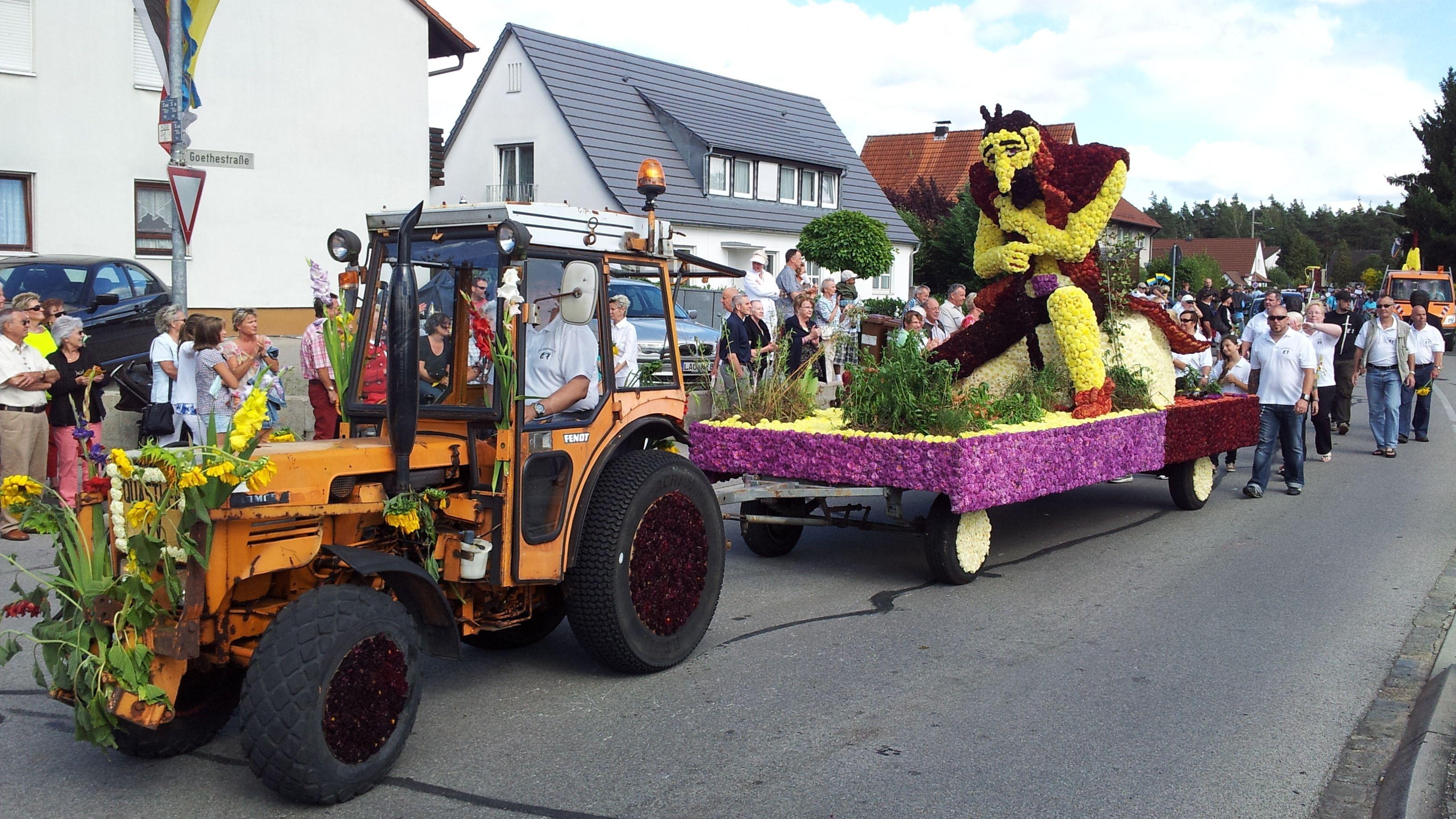 Ein Traktor zieht einen Festwagen, der mit Dahlienblüten geschmückt ist.