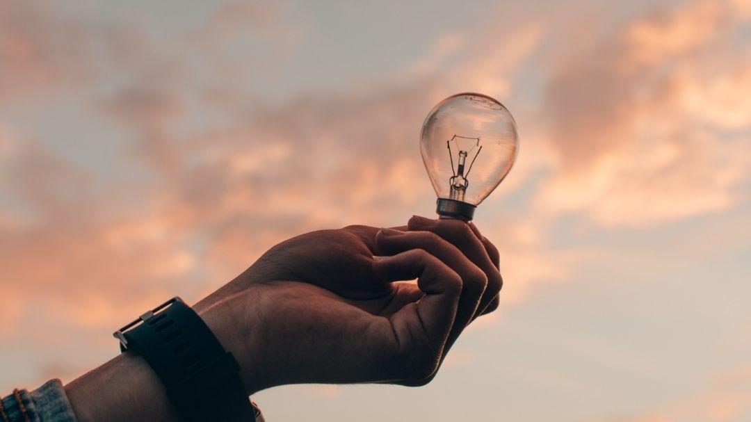 Hand hält Glühbirne in die Luft (Symbolbild).
