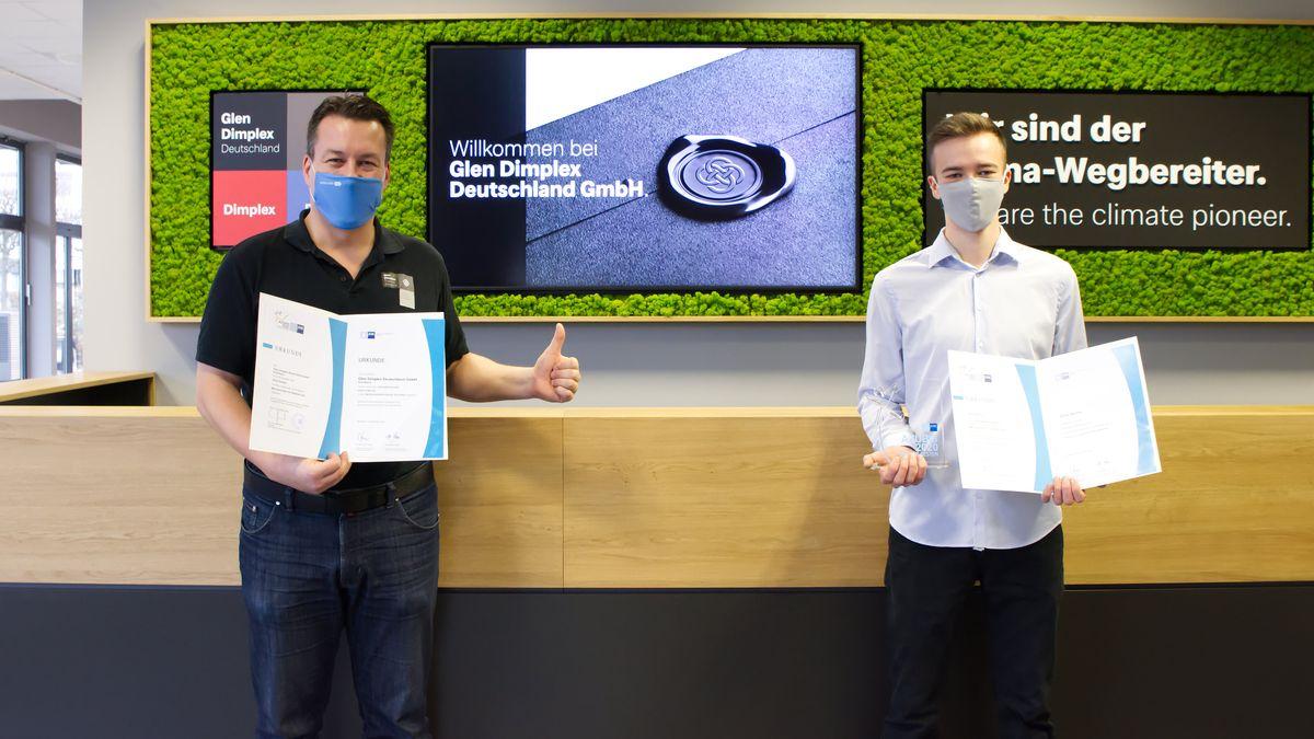Der Absolvent Dario Streller und sein Ausbilder Helmut Lauterbach halten die Abschlussurkunde der IHK ins Bild. Wegen Corona tragen beide einen Mund-Nase-Schutz.