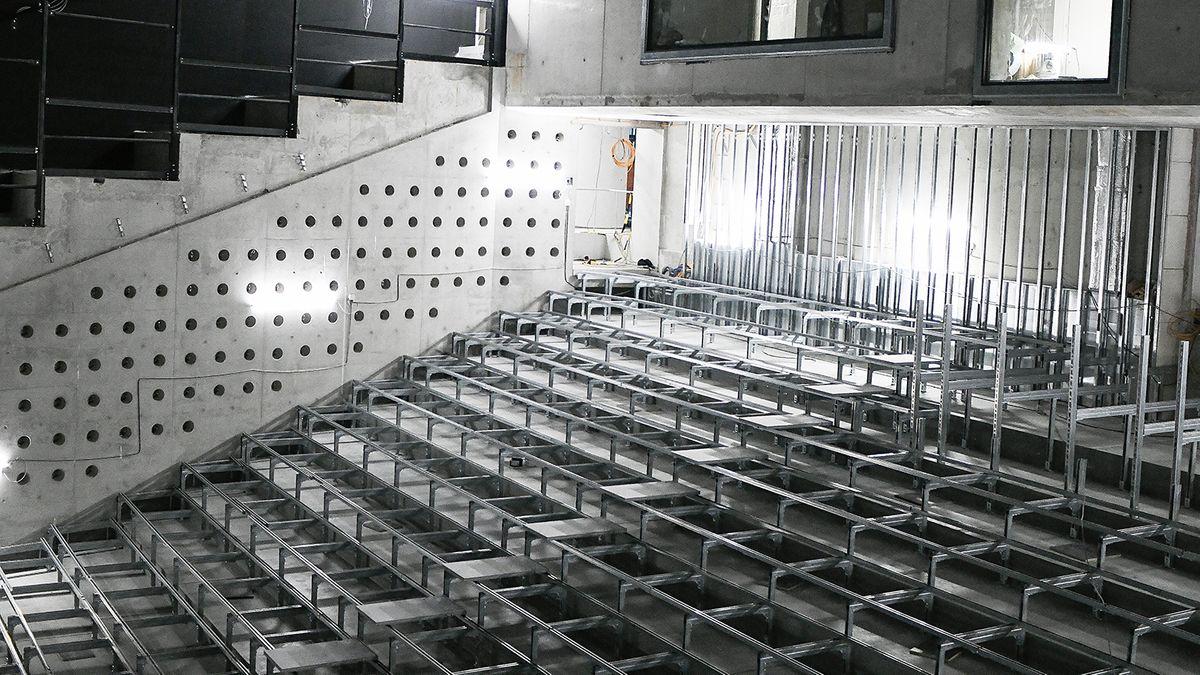 Stark ansteigende Sitzreihen im Zuschauerraum (Rohbau des neuen Volkstheaters von innen, Sitzreihen, Treppen an der Seite)