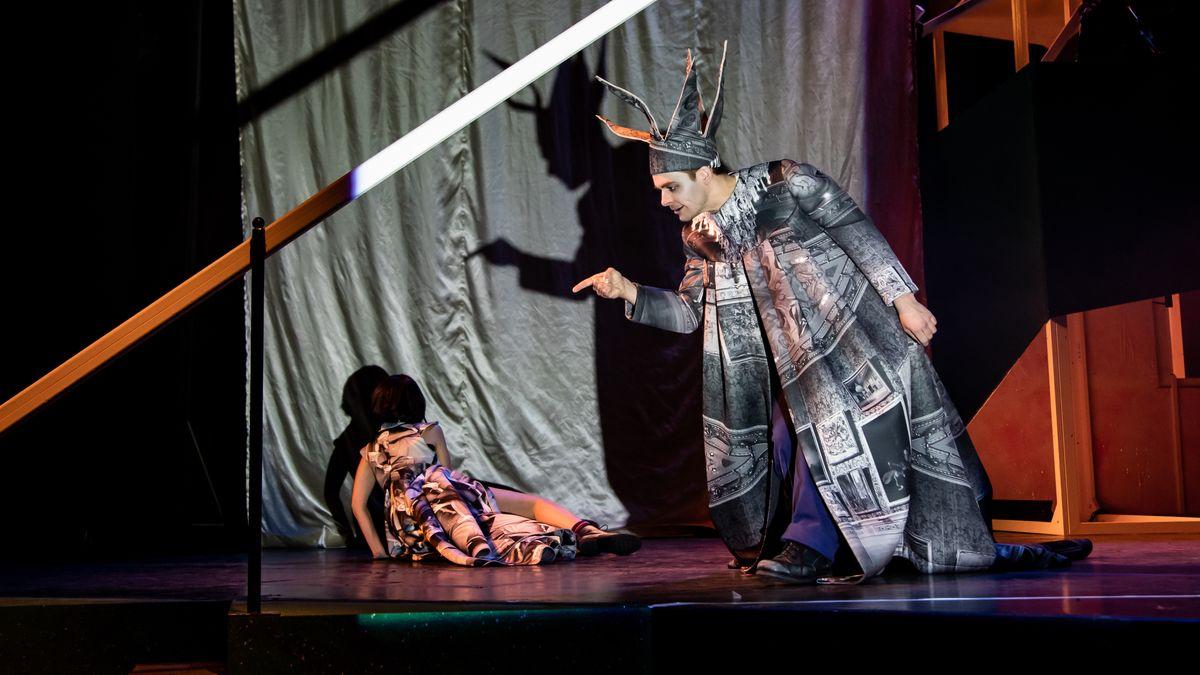 Ein Mann steht in Verkleidung auf einer Theaterbühne