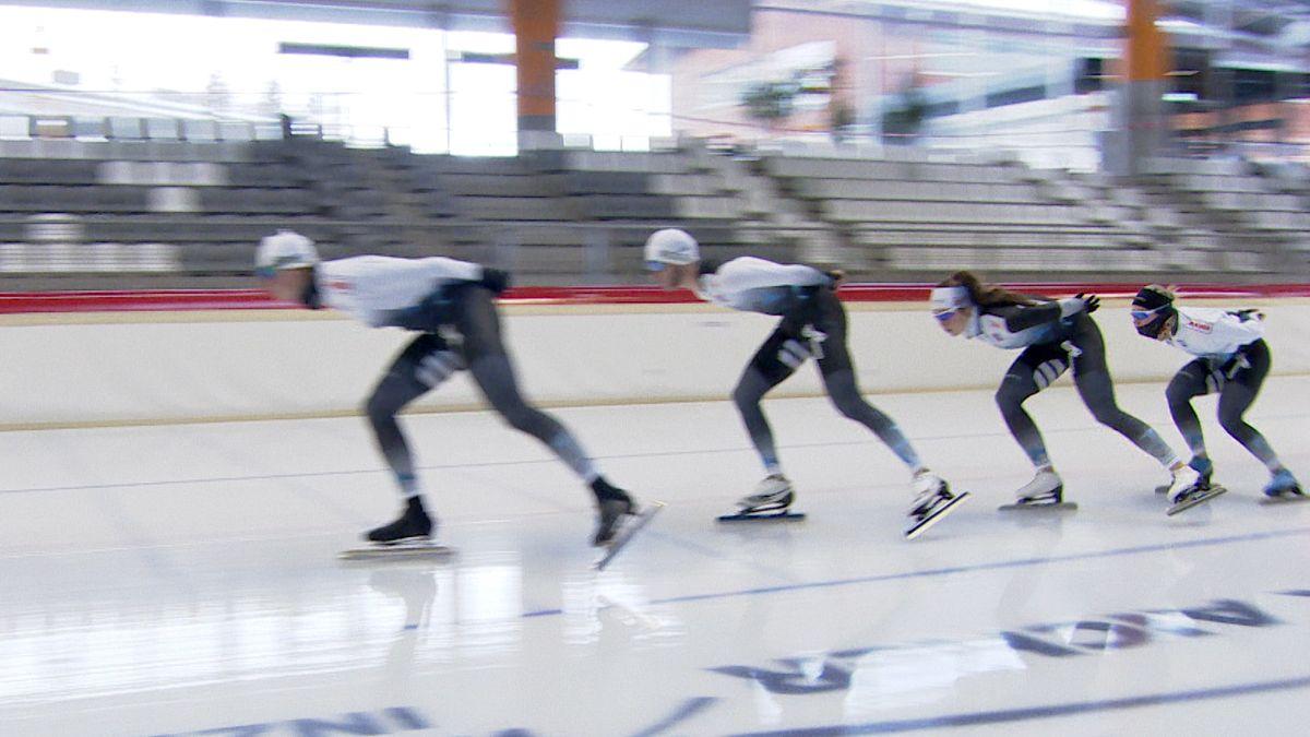Vier Eisschnellläufer laufen gebückt hintereinander her.