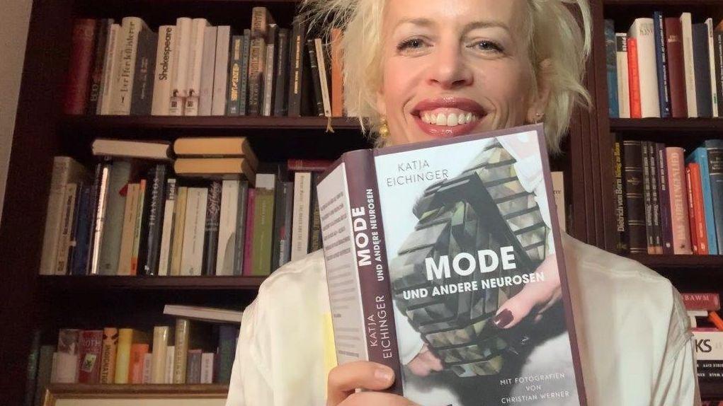 """Katja Eichinger hält ihr Buch """"Mode und andere Neurosen"""" in die Kamera, dahinter eine Bücherwand"""