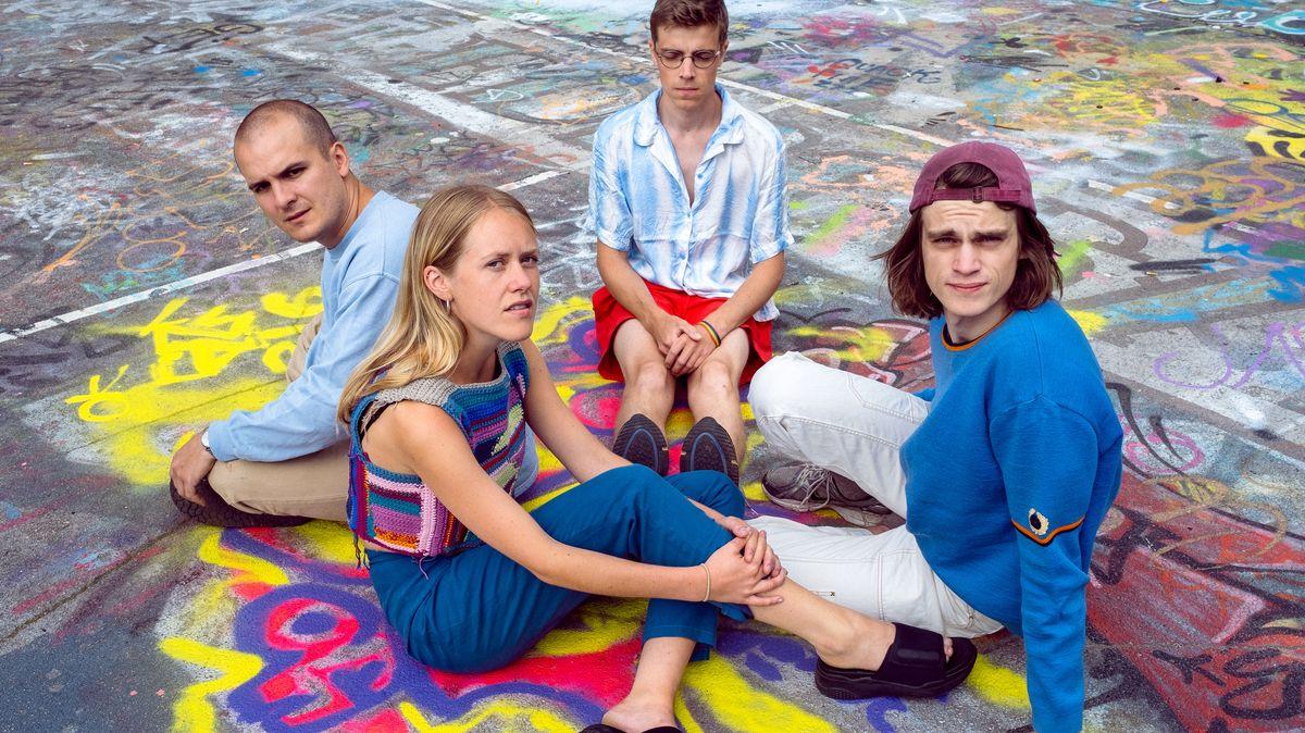 Man sieht vier junge Menschen auf einem mit Kreide-Graffitis bemalten Asphaltbelag sitzen - es sind die vier Mitglieder der Band Pom Poko.