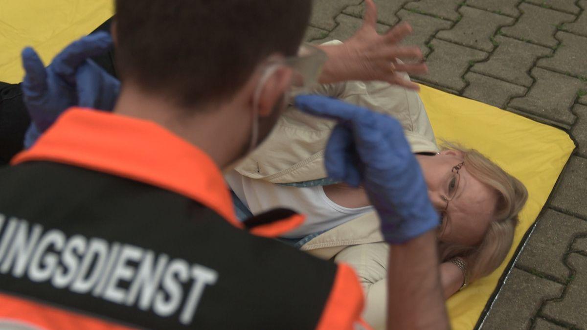 Ein Rettungssanitäter hilft bei einer Übung einer gehörlosen Frau, die am Boden liegt.
