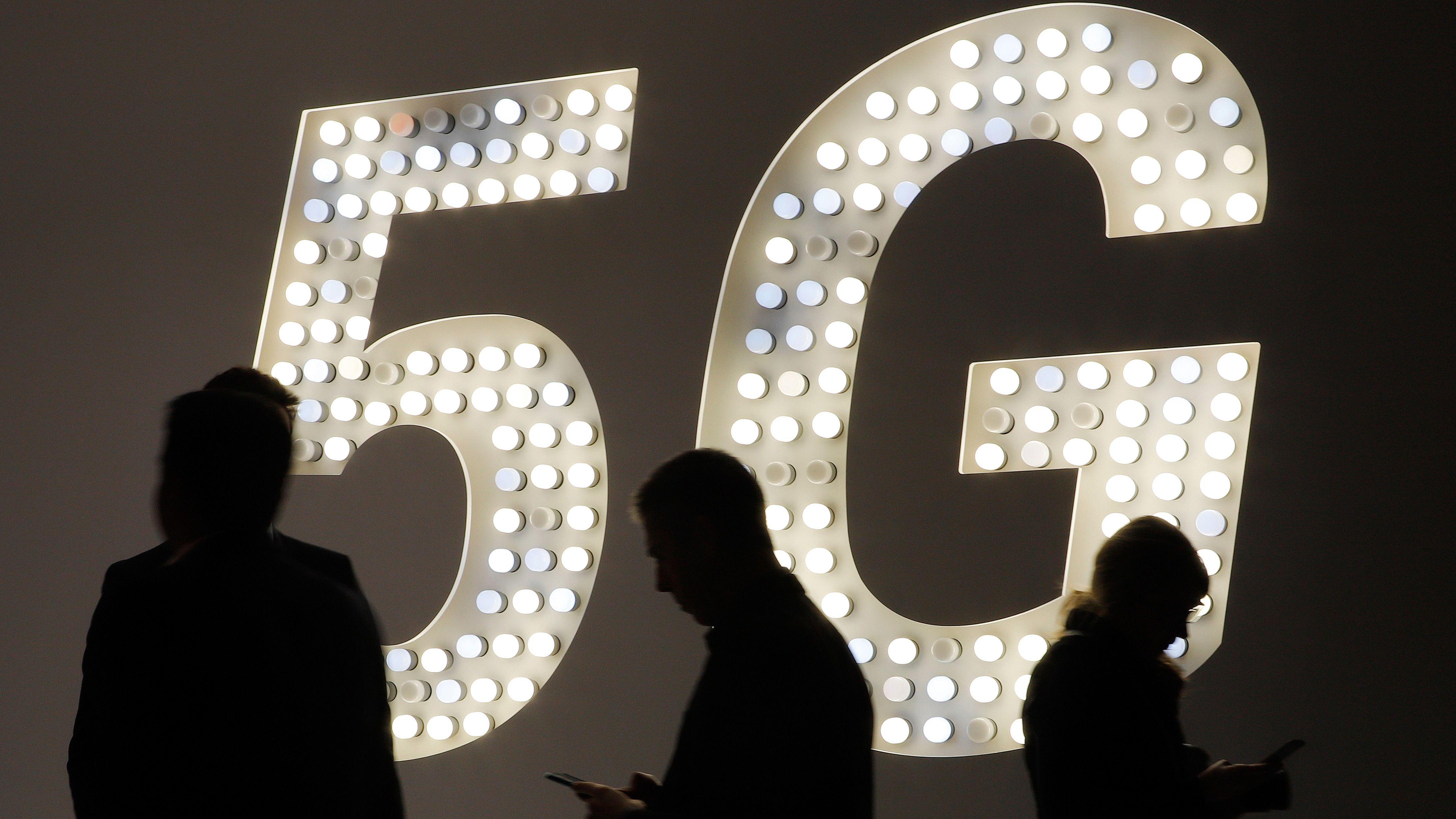 Barcelona: Besucher der Technikmesse Mobile World Congress gehen an einer Leuchttafel mit Werbung für den Mobilfunk-Standard 5G vorbei.