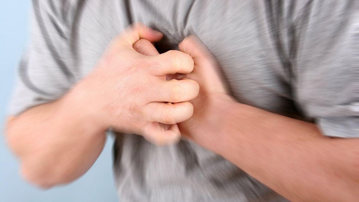 Anzeichen eines Herzinfarkts? Ein Mann hält sich die Brust vor Schmerzen.