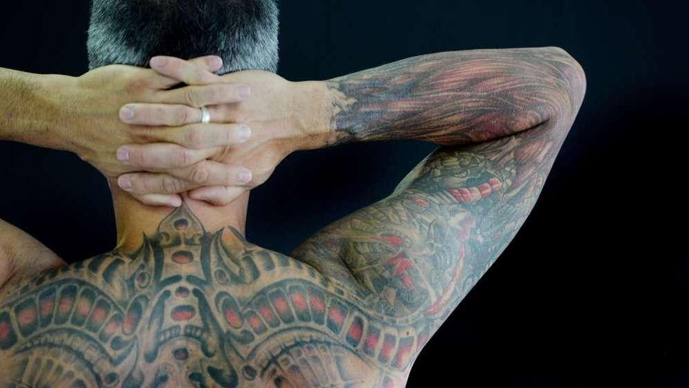 Ein Mensch mit Tatowierungen: Sein Rücken zeigt ein Skelett mit Muskeln, als würde man ihm unter die Haut blicken.