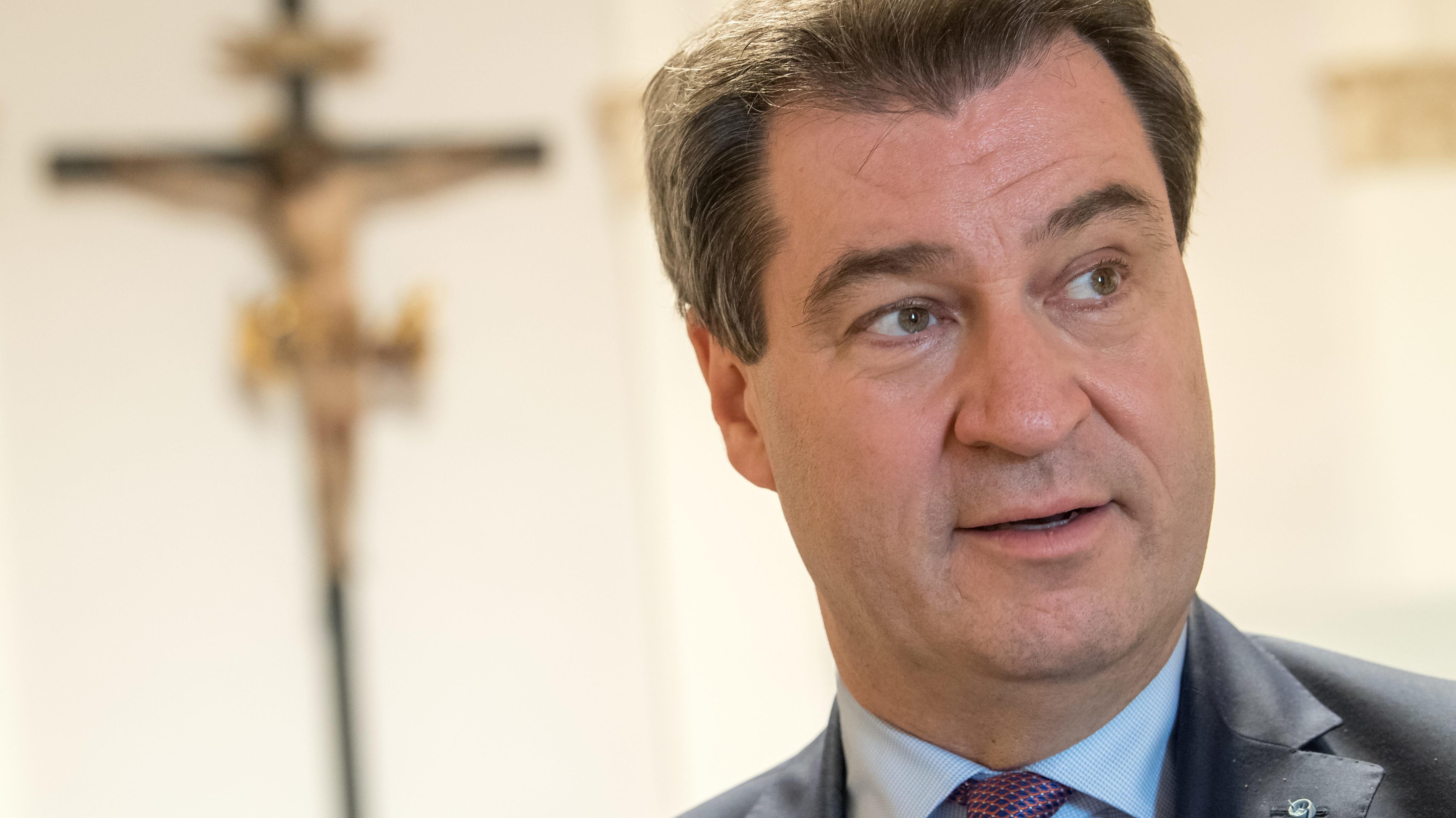 Ministerpräsident Markus Söder mit Kreuz im Hintergrund.