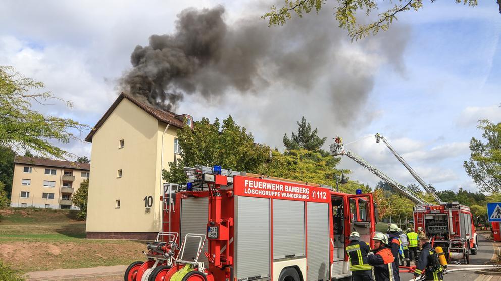 Feuerwehrautos stehen vor dem Ankerzentrum für Asylbewerber in Bamberg. Aus dem Dachstuhl des Hauses mit der Nummer 10 kommen  schwarze Rauchwolken.   Bild:News5