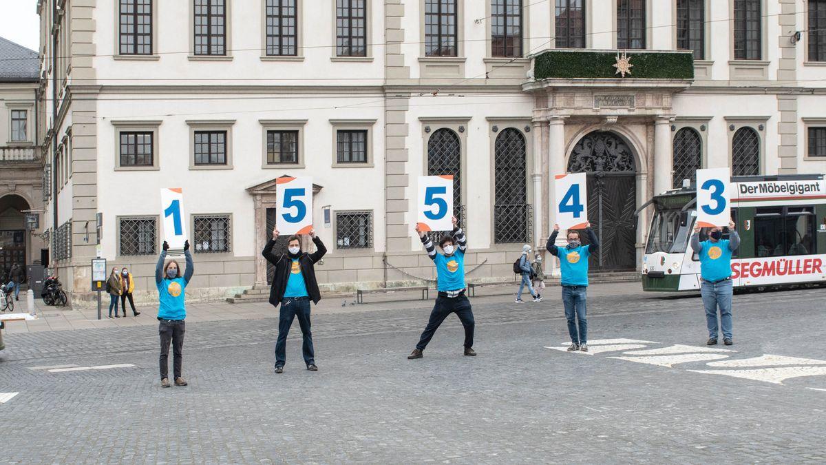 Vor dem Augsburger Rathaus halten fünf Menschen die Zahlen der erreichen Stimmen hoch.