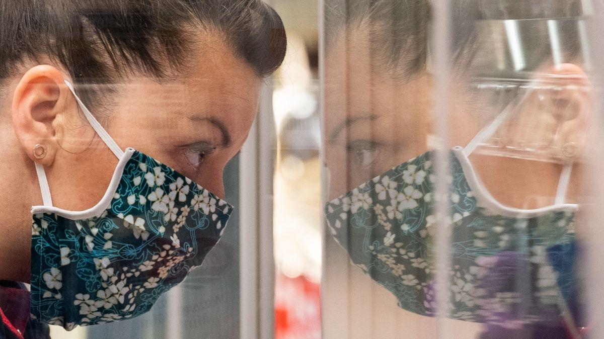 Eine Frau mit Mundschutz spiegelt sich in einer Glastür