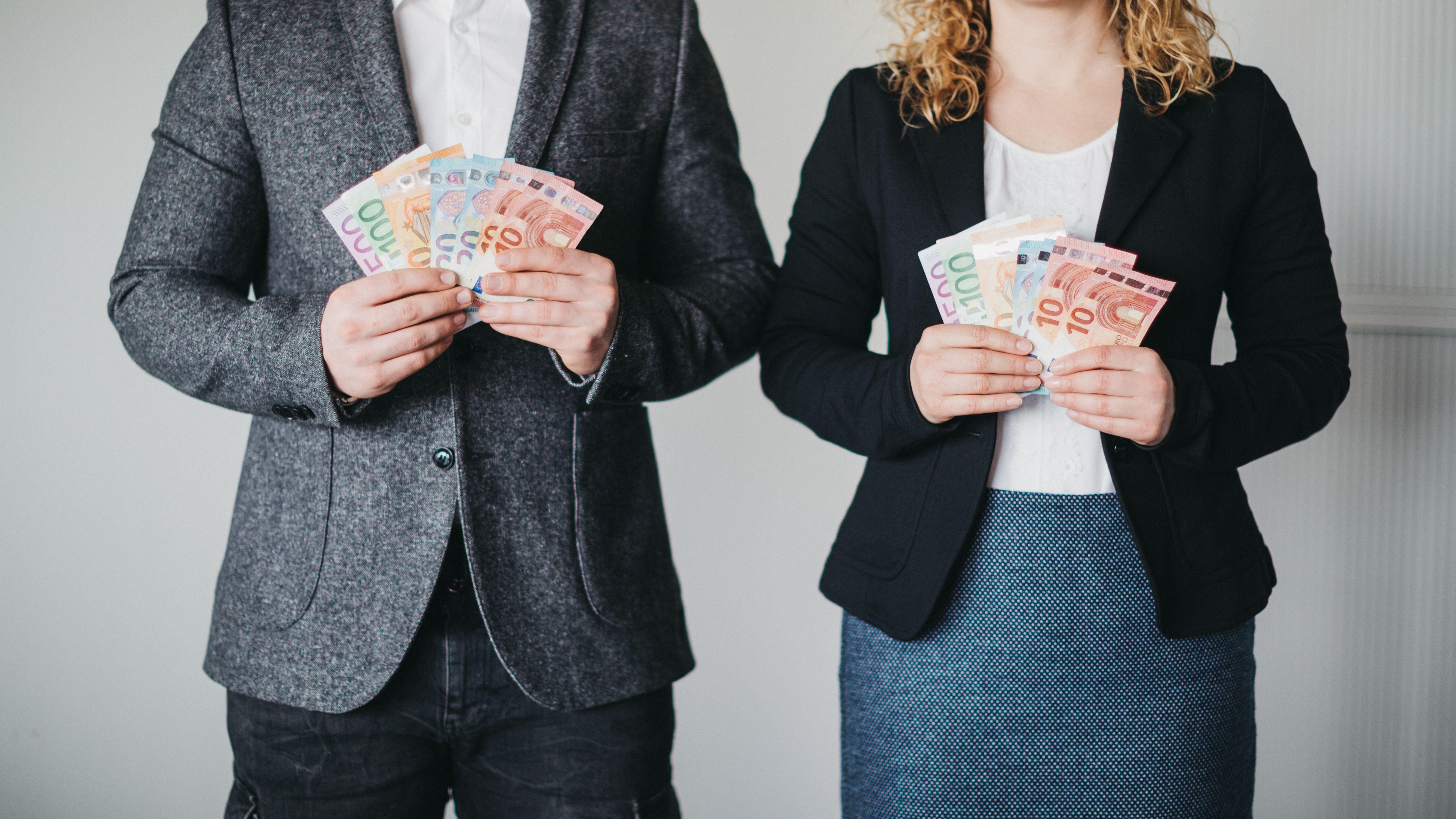 Mann und Frau halten Geldscheine in den Händen.