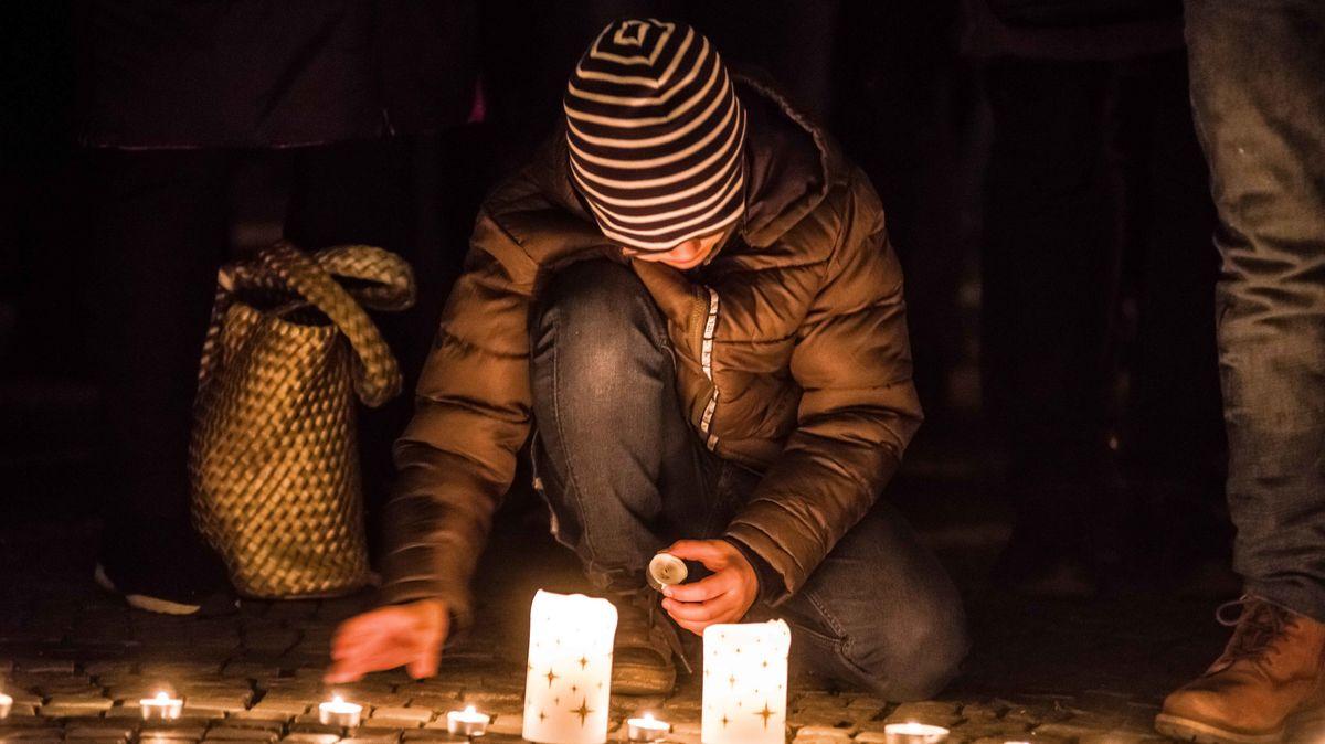 München: Ein Mann zündet am Odeonsplatz eine Kerze an.