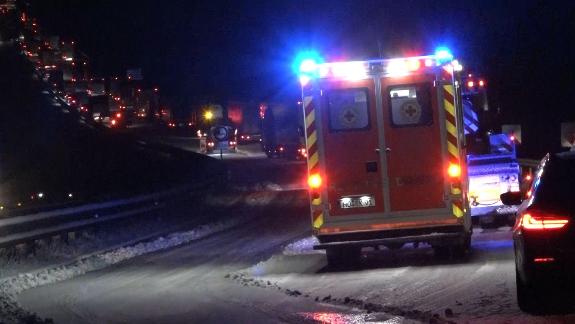 Ein Rettungswagen steht auf schneeglatter Fahrbahn, dahinter stehen Autos im Stau.