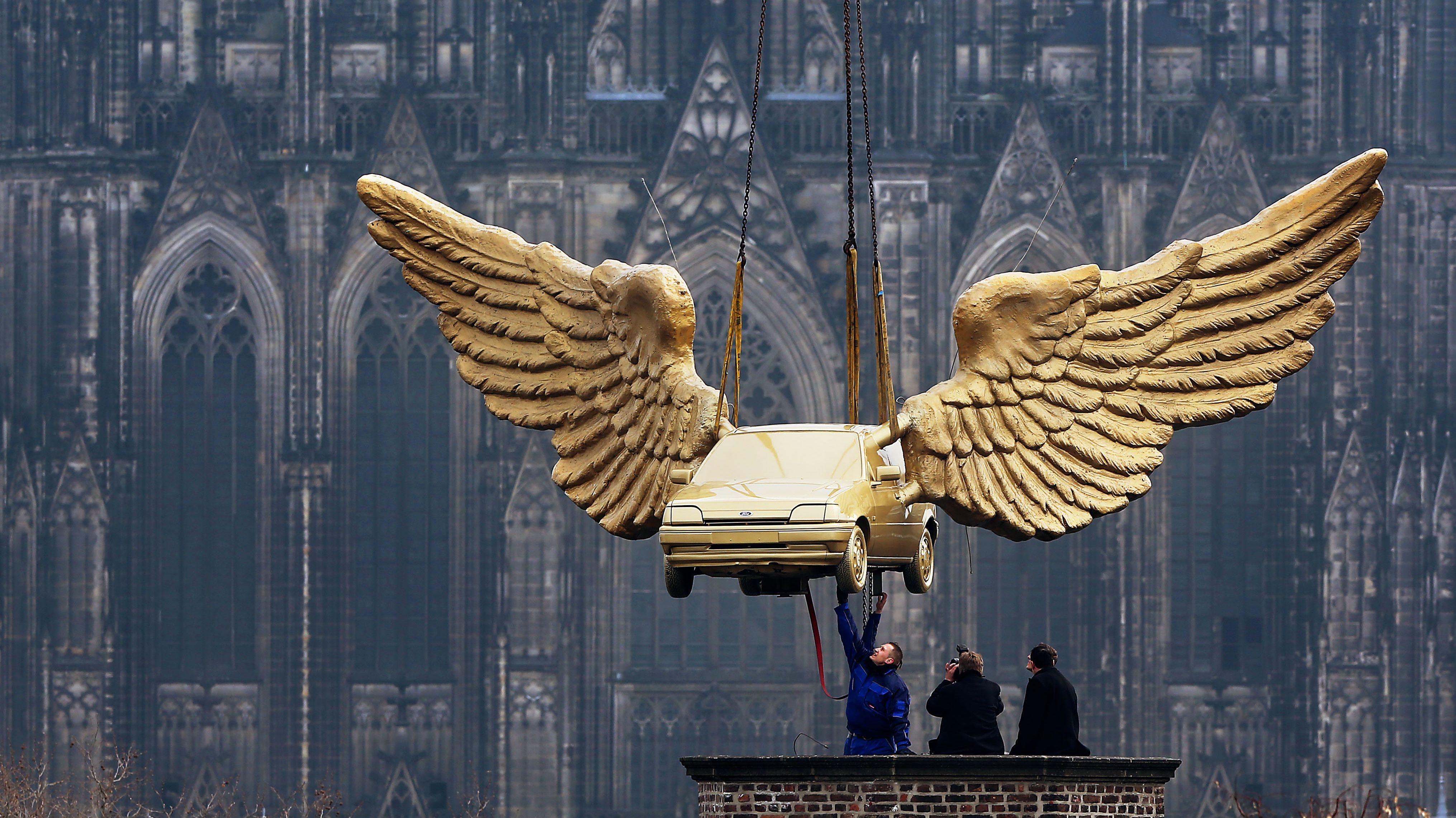 Arbeiter auf dem Dach des Kölner Stadtmuseums nehmen das restaurierte Flügelauto von HA Schult entgegen. Im Hintergrund: der Kölner Dom.