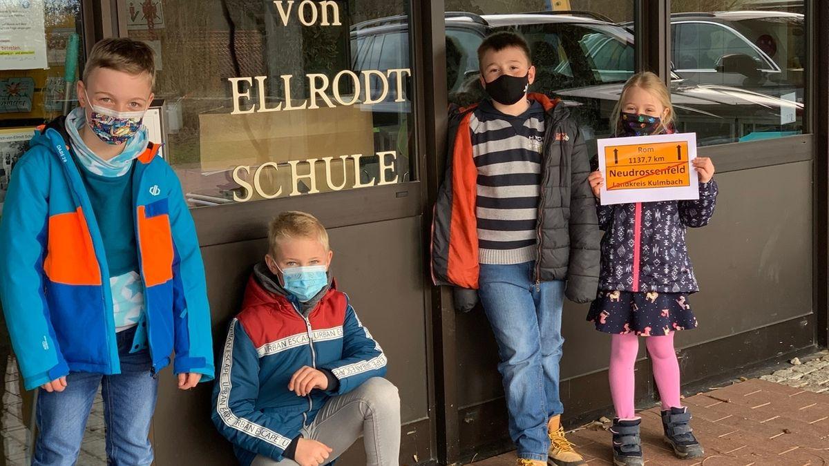 Vier Grundschüler mit Mund-Nase-Schutz vor ihrer Schule.