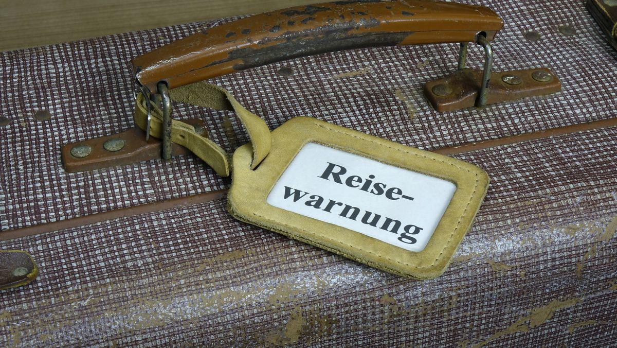Koffer mit Aufschrift Reisewarnung