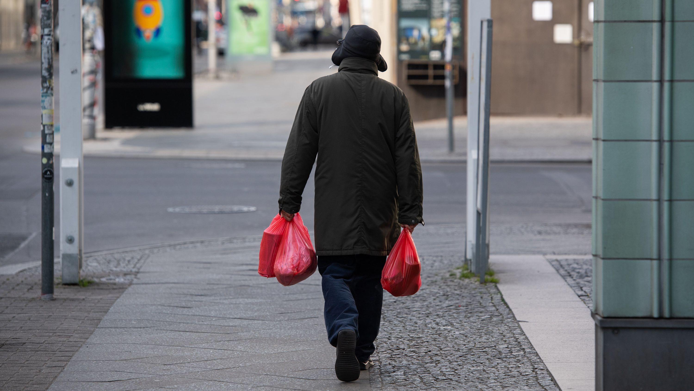 Ein Mann mit Einkaufstüten kehrt von Einkauf zurück