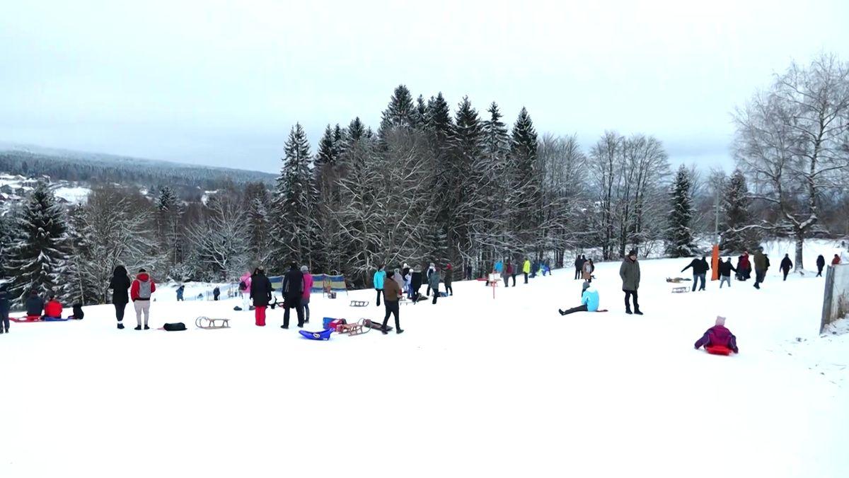 Kinder und Eltern stehen am Dreikönigstag an einem Hang im Fichtelgebirge.