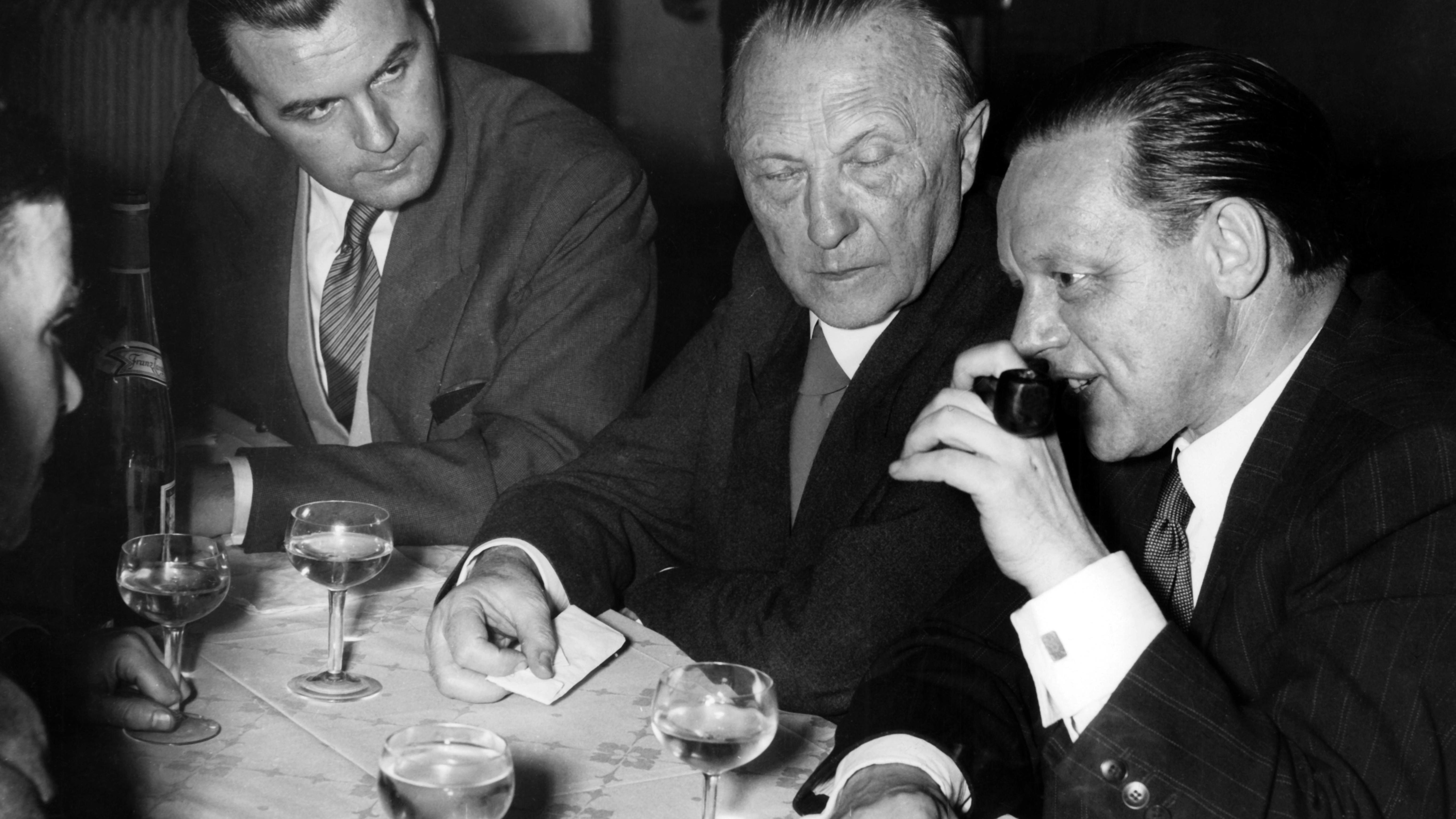 Bundeskanzler Konrad Adenauer (M) auf dem CDU-Parteitag im Oktober 1951 in Karlsruhe im Gespräch mit einem Journalisten (r). an einem Tisch voller Weingläser.