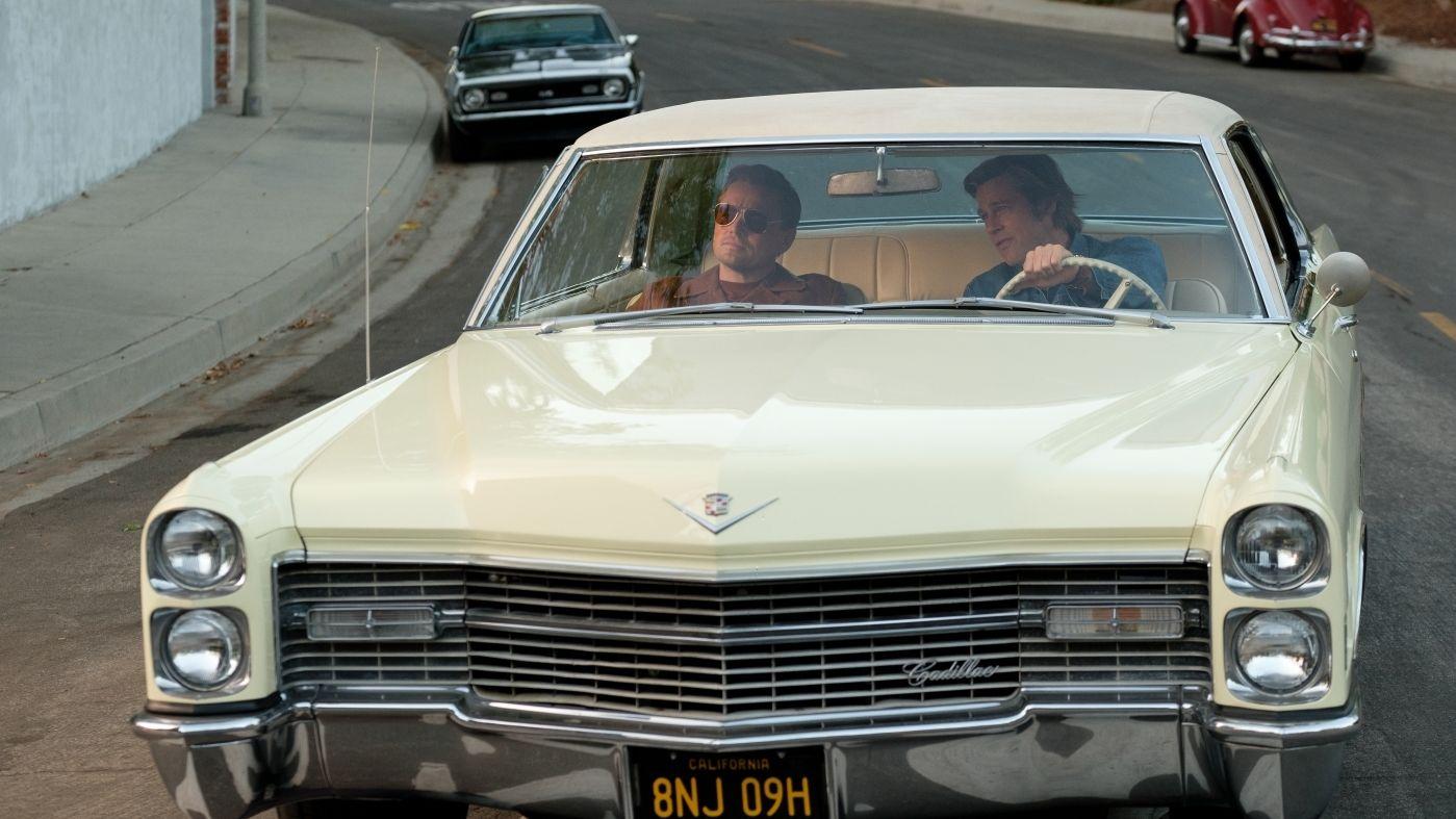 """Leonardo DiCaprio und Brad Pitt fahren in einem beigen Cadillac durch L.A. (Szenenfoto aus """"Once Upon a Time in Hollywood"""" von Quentin Tarantino)"""
