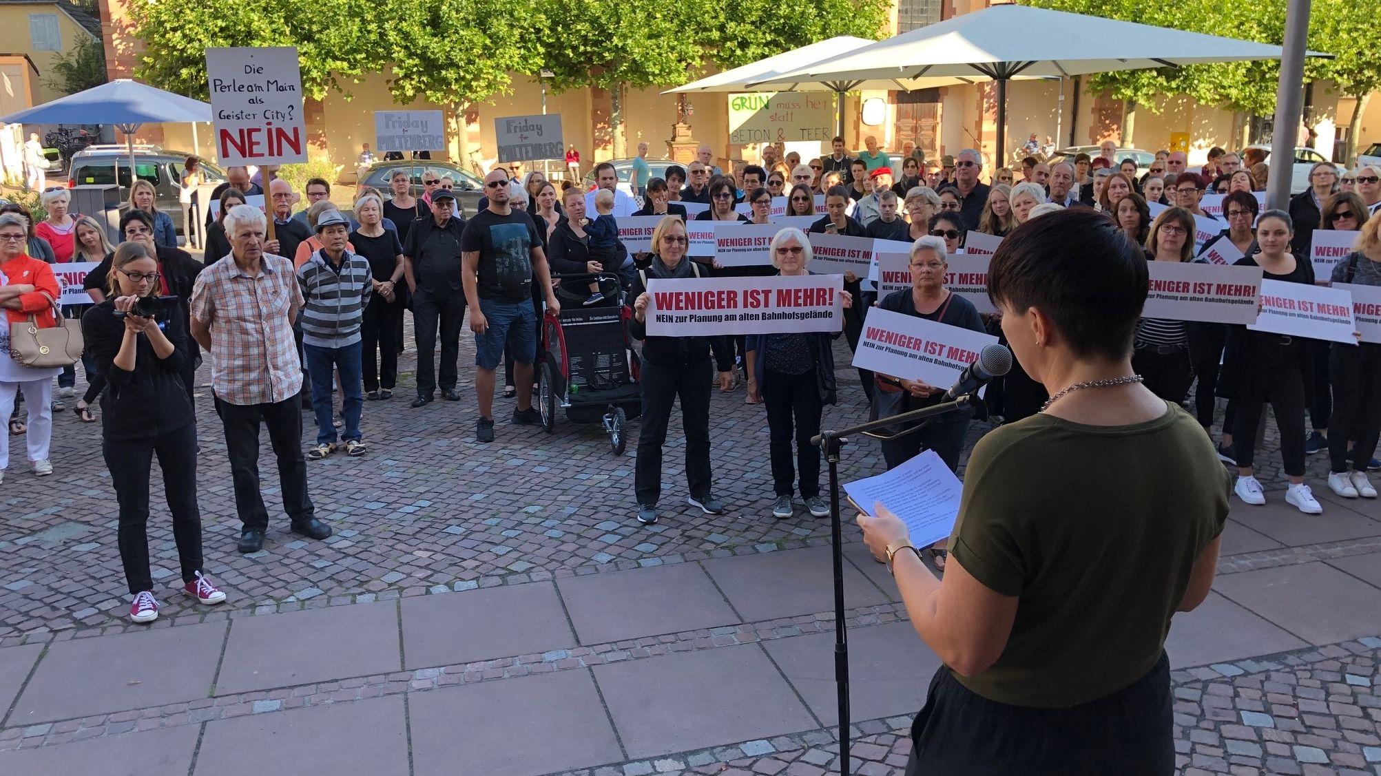 """Bei einer Kundgebung in der Innenstadt von Miltenberg halten Menschen Schilder mit der Aufschrift """"Weniger ist mehr"""" in den Händen."""